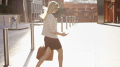 Attractive blonde business woman using smartphone commuting in city london - stock footage