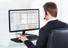 rear view of young businessman in headset using computer at office desk - stock photo