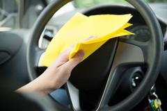 man's hand cleaning steering wheel of car with yellow microfiber cloth - stock photo