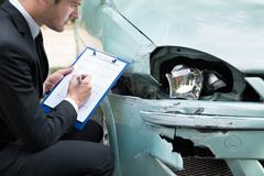 Side view of writing on clipboard while insurance agent examining car after a Stock Photos