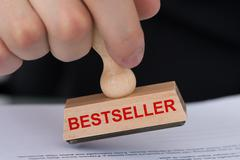 Closeup of hand stamping document with bestseller rubber stamp at table in of Stock Photos