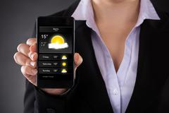 Close-up of businessperson showing weather forecast on mobile phone Stock Photos