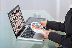 Stock Photo of cropped image of photo editor with color swatches working on laptop at desk