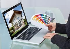 cropped image of photo editor holding color swatches while using laptop - stock photo