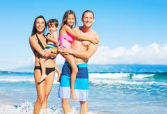 happy mixed race family on the beach - stock photo