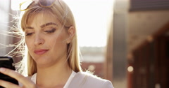 Beautiful blonde woman using smartphone solar flare sunlight energy concept - stock footage
