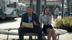 Business people talking on cellphone, reading newspaper on bench in city HD Stock Footage