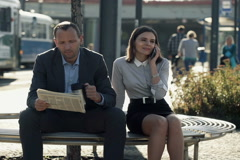 Business people talking on cellphone, reading newspaper on bench in city NTSC - stock footage