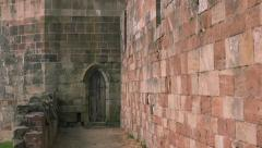 Stone castle wall pan reveal archway wooden door abandoned spaces Stock Footage
