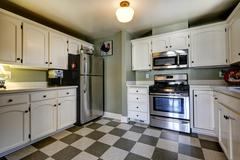 white kitchen cabinets and steel appliances. - stock photo