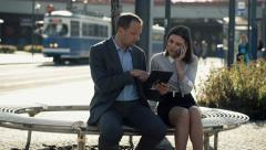 Business people with tablet and cellphone on bench in the city HD - stock footage