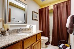 modern bathroom cabinet with granite top. brown curtains decorate the room - stock photo