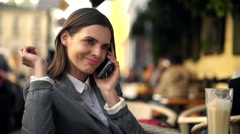 Busineswoman talking on cellphone and drinking coffee in cafe HD Stock Footage