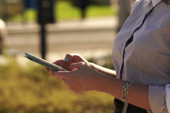 Businesswoman hands texting, sending sms on smartphone in the city NTSC - stock footage