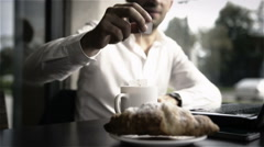 Business man making tea while working at desk with breakfast croissant Stock Footage