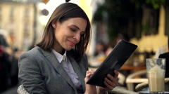 Pretty young businesswoman using tablet computer, sitting in cafe HD - stock footage
