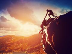 hikers climbing on rock, mountain at sunset, one of them giving hand and help - stock illustration
