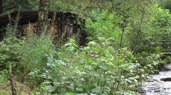 4k Old wooden bridge pan with wild river and house in forest Stock Footage