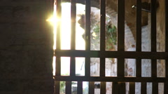 Glare of sunlight through bars  ancient gates fortress - stock footage