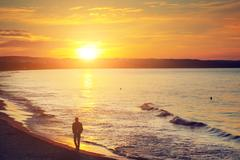 Man walking alone on the beach at sunset. calm sea with rippling waves. Stock Photos