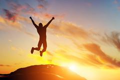 Happy man jumping for joy on the peak of the mountain, cliff at sunset. succe Piirros