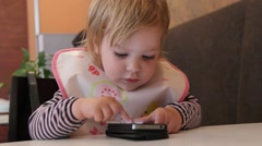 Cute two year old blond girl plays with mobile phone Stock Footage