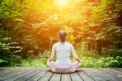 young woman meditating in a forest sitting on a wooden floor. zen, meditation - stock photo
