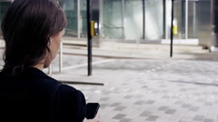 Attractive business woman commuter using smartphone walking in city of london Arkistovideo