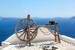 Old craftsmanship machine on the roof of the building on santorini, greece Stock Photos