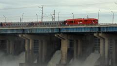 Passenger train Russian Railways rides on the dam Stock Footage