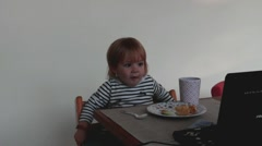 Cute little  girl in a striped blouse eating and watching cartoon Stock Footage