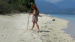 Girl drawing shapes in sand Stock Footage
