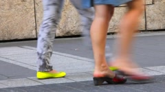 Past the camera  pedestrians coming and the viewer sees only their feet - stock footage