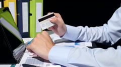 Business man paying with credit card by tablet, on black background Stock Footage