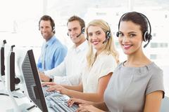 Business people with headsets using computers in office - stock photo