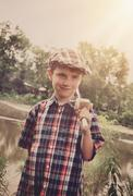 little boy with wooden fishing pole by pond - stock photo