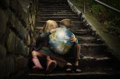 children holding earth planetin secret - stock photo