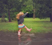 Child splashing in dirty mud puddle Stock Photos