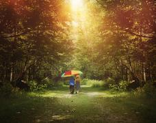 children walking in sunshine woods with umbrella - stock photo