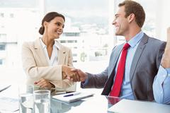 Executives shaking hands in board room meeting - stock photo
