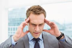 Businessman with severe headache at office - stock photo