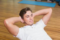 Stock Photo of Man doing sit up on exercise ball