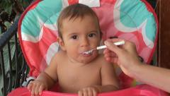Baby eats cottage cheese with screwed up face Stock Footage