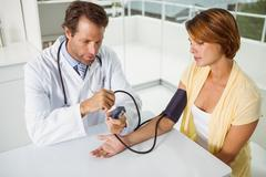 Doctor checking blood pressure of woman at medical office Kuvituskuvat