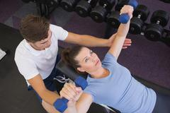 Stock Photo of Personal trainer helping client lift dumbbells