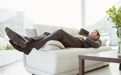 Young businessman lying on couch - stock photo