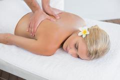 Stock Photo of Woman receiving back massage at spa center