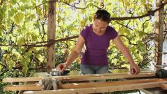 Woman measuring wood plank with metal joiner meter Stock Footage