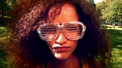 Young Latino woman wearing silly light up glasses dancing around in a park Stock Footage