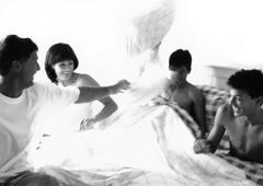 Family having pillow fight in bed, b&w Stock Photos